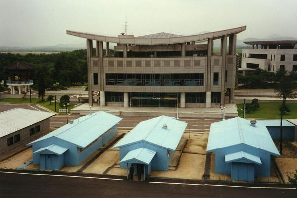 Three light blue buildings with the modern South Korean border post at Panmunjom | North Panmunjom | North Korea