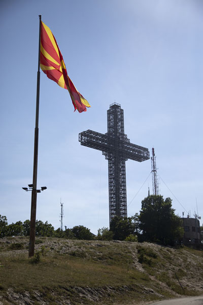 Foto van The North Macedonian flag with the Millennium cross in the backgroundSkopje Millenniumkruis - Noord-Macedonië