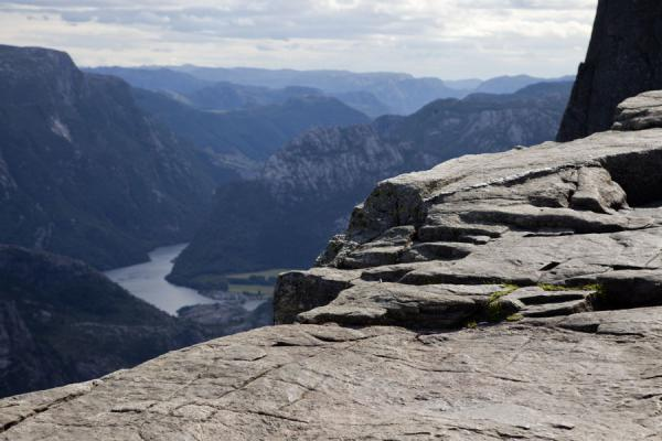 The rocky surface of Preikestolen in the foreground; mountains and fjords below | Preikestolen (Roca púlpito) | Noruega