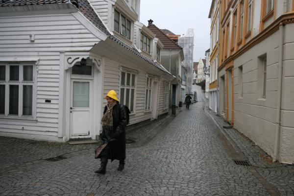 Woman with popular rain protective hat in a typical street | Rainy Bergen | Norway