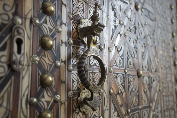 Foto van Close-up of richly decorated wooden door on a wall in Bait al OudMuscat - Oman