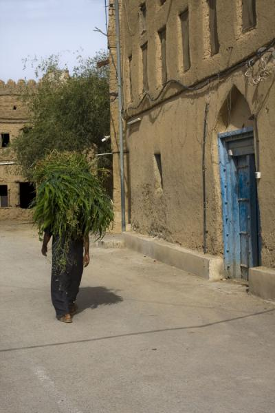 Omani man walking past an adobe building in the old part of Al Hamra | Hamra Old Town | Oman