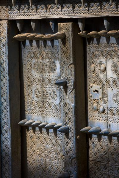 Picture of Blue decorated wooden door with spikes in the old town of Hamra