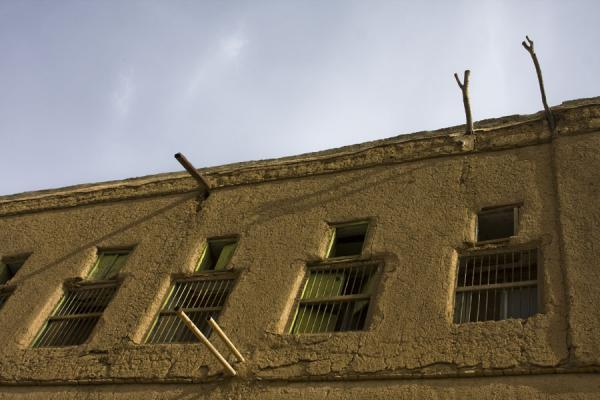 Windows and wooden sticks in one of the many adobe buildings in Hamra | Hamra Old Town | Oman