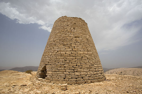 One of the tall beehive tombs under a partly cloudy sky | Jaylah beehive tombs | Oman