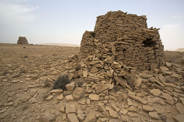 Partly collapsed beehive tomb with other tomb in the background | Jaylah beehive tombs | Oman