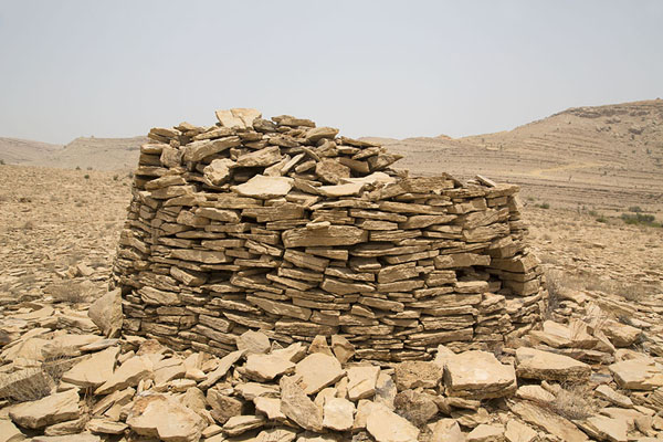Collapsed beehive tomb surrounded by stones | Jaylah beehive tombs | Oman