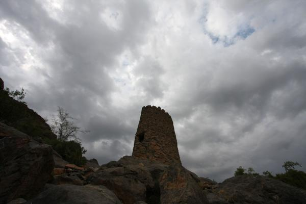 Defensive tower under a cloudy sky at Misfat | Misfat | Oman