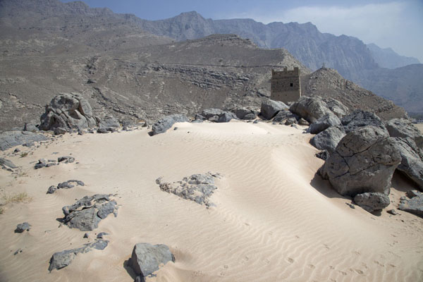 Foto di Stretch of sand and an old watchtower behind, at the top of a hill overlooking the Musandam coastMusandam Peninsula - Oman