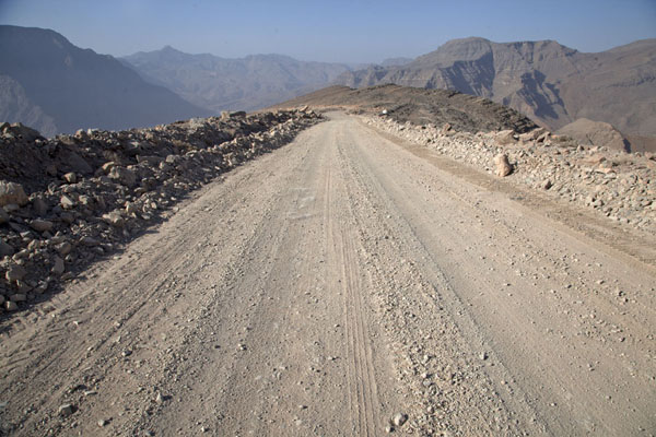 Gravel track running down towards Wadi Bih and United Arab Emirates | Musandam mountains | Oman