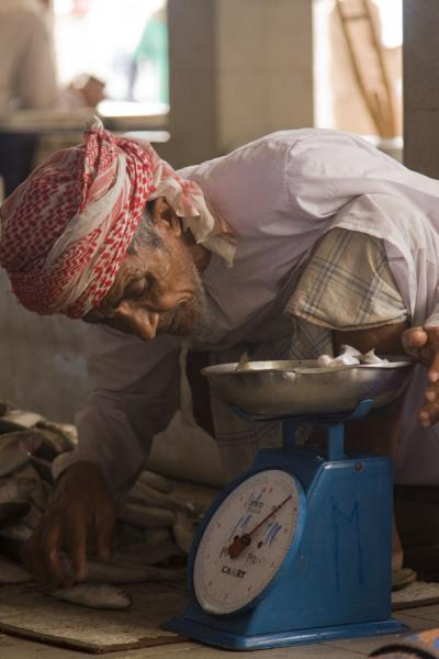 Old Omani checking the scale | Mutrah Fish Suq | Oman