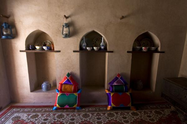 Pillows and oil lamps on a side wall of a room inside Nakhal Fort | Nakhal Fort | Oman