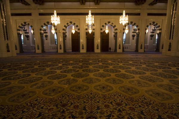 Picture of Sultan Qaboos Grand Mosque (Oman): Arches, chandeliers, and part of the enormous carpet in the main prayer hall