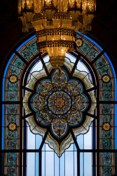One of the stained glass windows with chandelier in the main prayer hall | Sultan Qaboos Grand Mosque | Oman