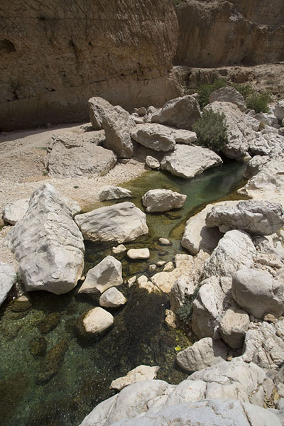 Water streaming down through rocks and boulders in the wadi | Wadi Bani Khalid | Oman