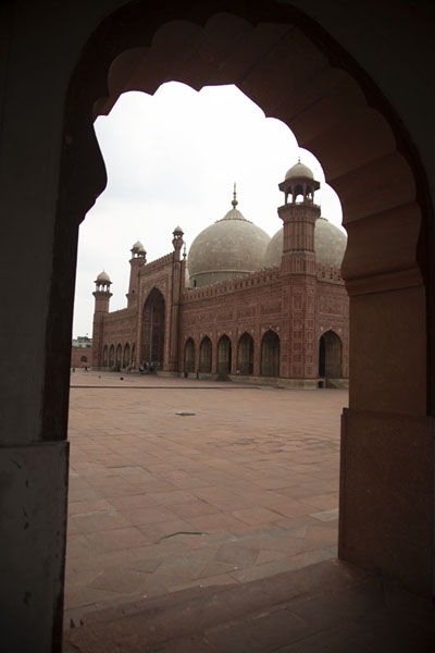 Photo de Badshahi Mosque seen through one of the arches in the corridor on the sideLahore - Pakistan