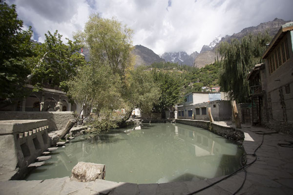 Foto van Small pond surrounded by buildings at the edge of the old town of GanishGanish - Pakistan