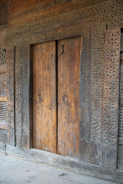 Picture of Wall and door with wood carvings in one of the old mosques of Ganish
