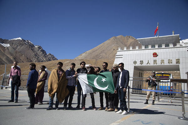Foto di People posing with the Pakistani flag in front of the Chinese border at KhunjerabKhunjerab - Pakistan