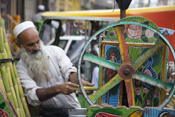 Old man making sugar cane juice using his colourful cart | Pesjawar oude stad | Pakistan
