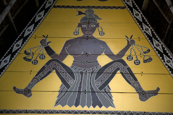 Foto van Close-up of female figure painted on yellow background on the bai of AimeliikBabeldaob - Palau