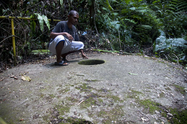 Foto van Guide sitting on the disk of stone money at the quarryNgurusar Bay - Palau