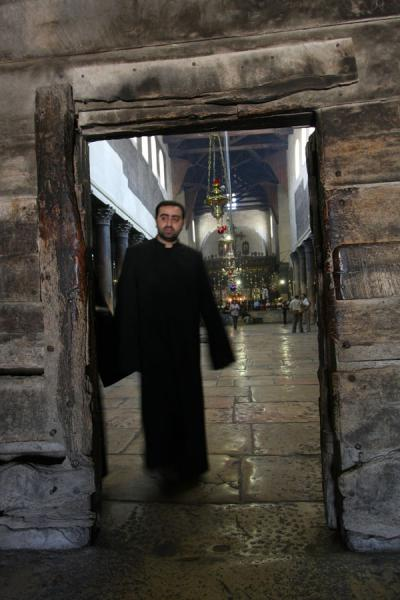 Armenian priest exiting at the Door of Humility | Church of the Nativity | Palestinian Territories
