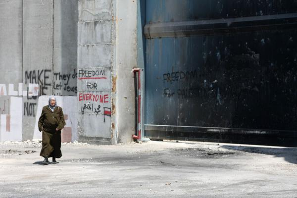 Foto di Palestinian woman walking past a gate in the Israeli wallBetlemme - Palestina
