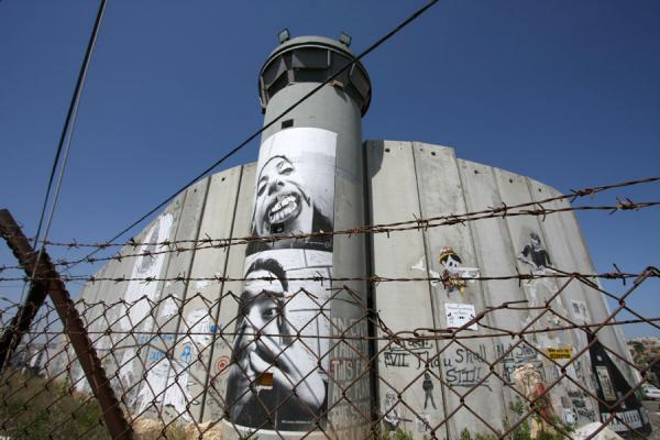 Picture of Israeli Wall (Palestinian Territories): Wall covered by creative spirits, watchtower, and barbed wire