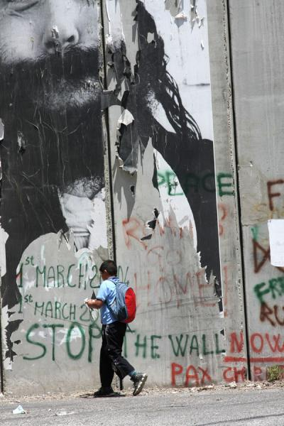 Picture of Israeli Wall (Palestinian Territories): Boy walking past the monstrous wall in Bethlehem