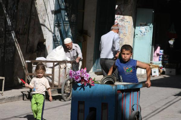 Picture of Boy and old man pushing a cart through a street of Nablus