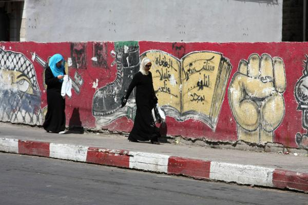 Women walking past a wall with artistic statements in Ramallah | Palestinians | Palestinian Territories