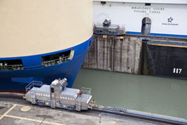Locomotives pulling a large cargo ship through the Miraflores locks | Panama Kanaal | Panama