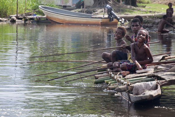 Boys fishing from a canoe at the shore of the lake of Angoram | Angoram | Papua Nuova Guinea
