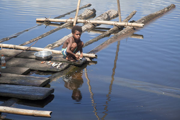 Picture of Angoram (Papua New Guinea): Small boy washing dishes in the lake at Angoram