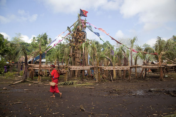 Man carrying yams in front of a tall pile of yams in the middle of Gumilababa | Gumilababa Festiviteiten | Papoea Nieuw Guinea