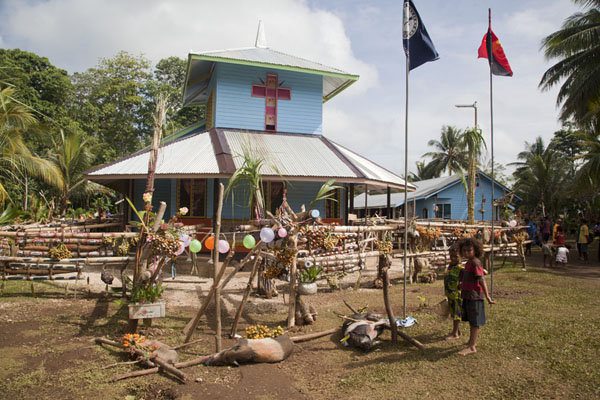 Pigs waiting to be slaughtered in front of the new church | Festività Gumilababa | Papua Nuova Guinea
