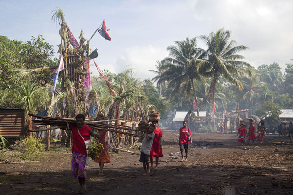 People dressed in red carrying yams and betel nuts for the festivities | Gumilababa Festiviteiten | Papoea Nieuw Guinea