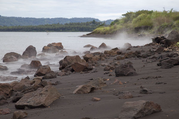 Beach with volcanic sand, rocks, and hot sea at the feet of Tavurvur volcano | Matupit grootpoothoender ei jagers | Papoea Nieuw Guinea
