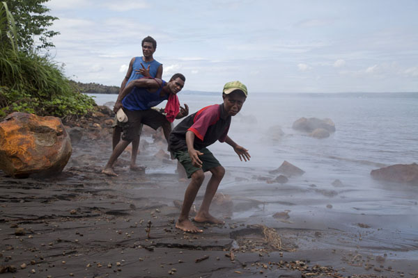 Young men from Matupit in the steam of the hot sea at the beach | Matupit megapode egg gatherers | 巴布亚新畿内亚