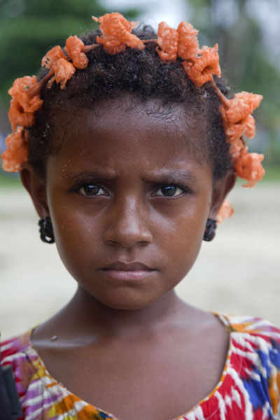 Young girl with flowers in Kaibola on Kiriwina island | Los Papuas | Papúa Nueva Guinea
