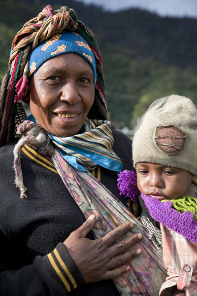 Woman with child dressed up for the cold of the highlands | I Papua | Papua Nuova Guinea