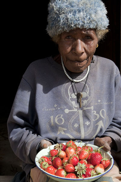 Foto van Old woman showing a tray of strawberriesPapuas - Papoea Nieuw Guinea