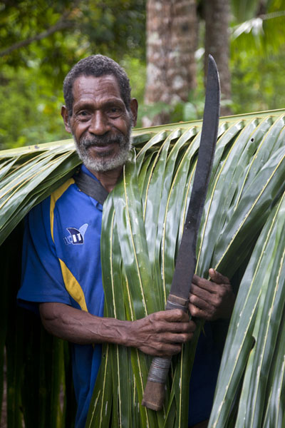 Foto van Man with machete and palm tree leafPapuas - Papoea Nieuw Guinea