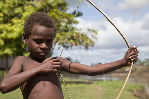 Picture of Papua New Guineans (Papua New Guinea): Young boy with arrow near the Sepik river town of Angoram