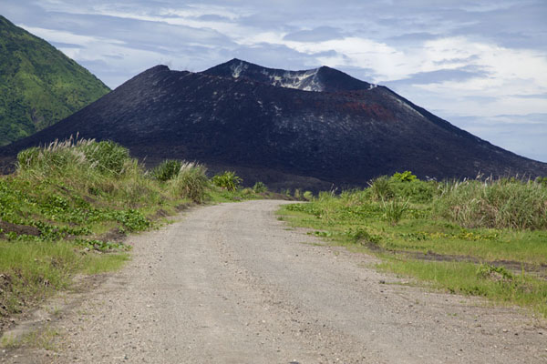Picture of Black Tavurvur contrasting with the road and vegetation - Papua New Guinea - Oceania