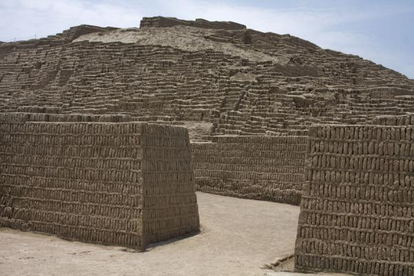 Some of the walls of the buildings with the pyramid in the background | Huaca Pucllana | Peru