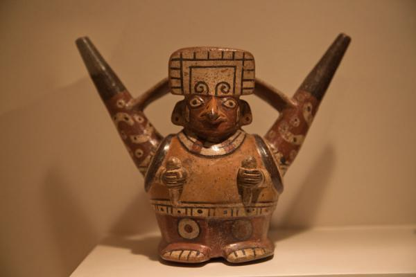 Foto van Typically red-and-white painted pottery representing a human figureLima - Peru