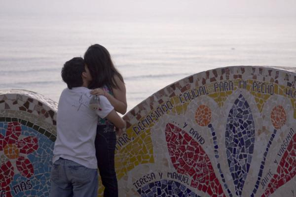 Picture of Parque del Amor (Peru): Couple cuddling and kissing at sunset in colourful Parque del Amor