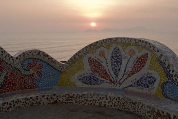 Sunset over the Pacific with bench of the Parque del Amor in the foreground | Parque del Amor | Peru